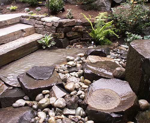 Landscape steps and rock water feature by Environmental Construction